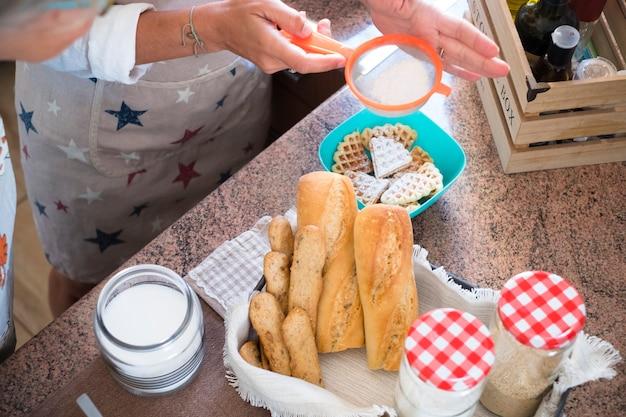 Nonna e figlia che cucinano a casa - si divertono e si divertono insieme al coperto - e la nonna sta mostrando come cucinare spuntini - ingredienti