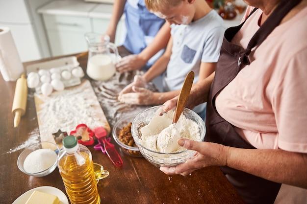Nonna e bambini entusiasti che preparano insieme l'impasto dei biscotti