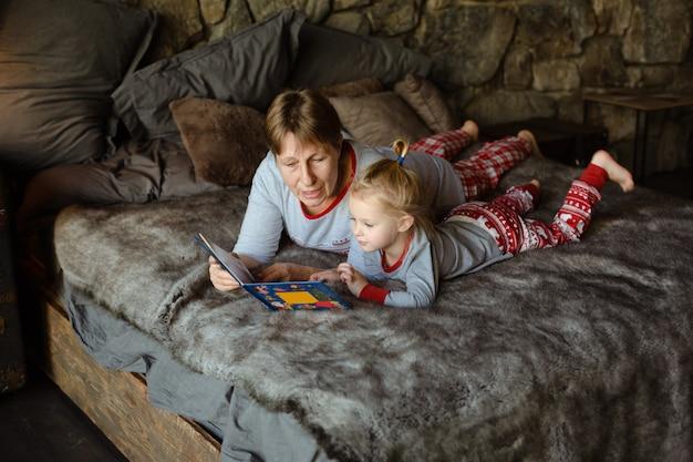 Nonna e nipote si divertono insieme a leggere un libro sul letto