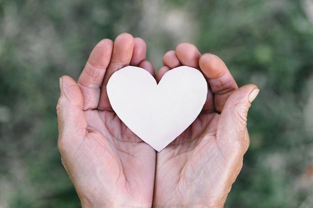 La mano della nonna tiene un cuore