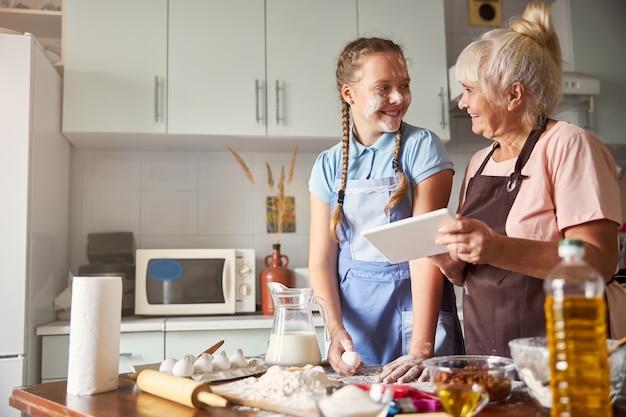 La nonna condivide le sue conoscenze di cottura con la nipote allegra