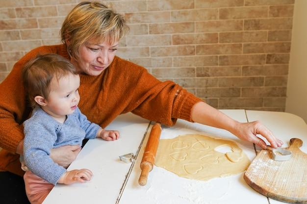 Nonna che prepara gustosi biscotti dolci insieme a sua nipote per il giorno di san valentino, carina piccola ragazza del bambino, seduto al tavolo in cucina