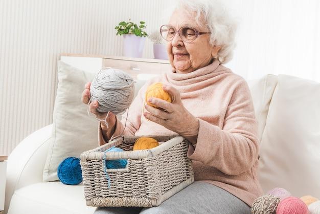 Nonna che sceglie palline di lacci colorati dal cestino