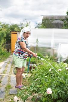 Nonna nel paese innaffiando i fiori