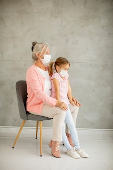 Nonna e nipotina carina che indossa una maschera respiratoria
