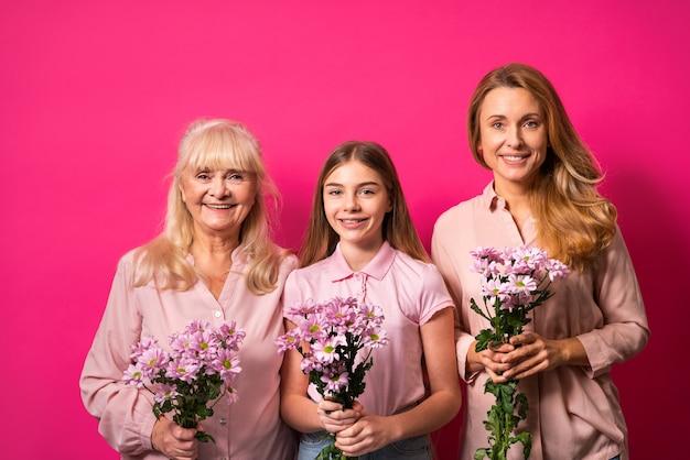 Nonna, figlia e nipote che tengono insieme un mazzo di fiori