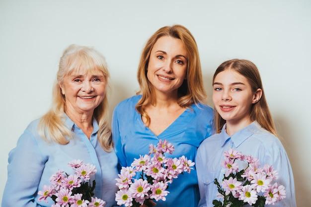 Nonna, figlia e nipote insieme a casa tenendo il mazzo di fiori