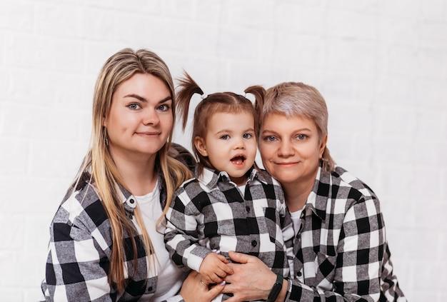 Nonna, figlia e nipote, tre generazioni di donne su una superficie bianca