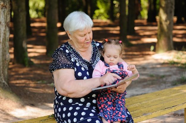 Nonna e nipote che leggono il libro nel parco