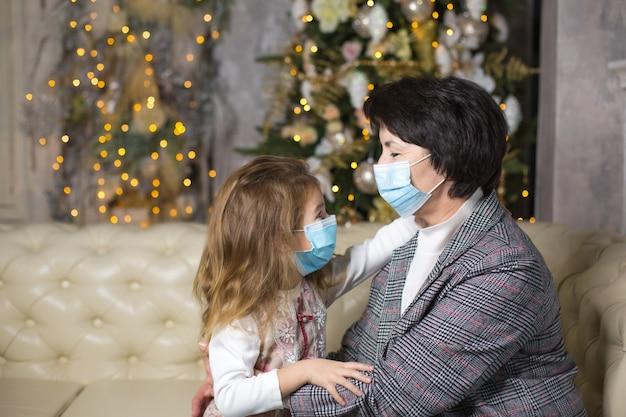 Nonna e nipote sul divano del soggiorno con decorazioni natalizie che abbracciano maschere mediche sui loro volti. una vacanza in famiglia durante l'epidemia di coronavirus e malattia. nuovo anno