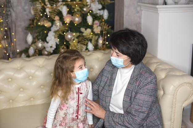 Nonna e nipote sul divano del soggiorno con decorazioni natalizie che abbracciano maschere mediche sui loro volti.
