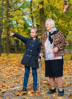 Nonna e nipote che camminano nella sosta di autunno