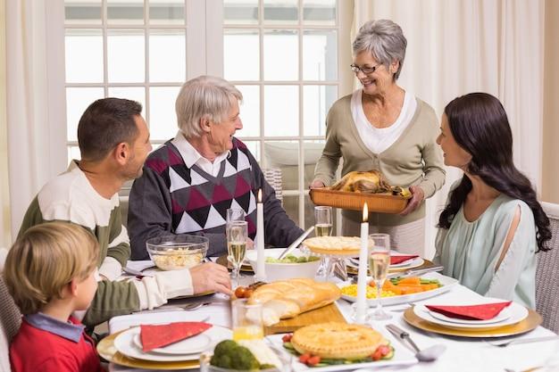La nonna che tiene arrosto di tacchino con la famiglia al tavolo da pranzo