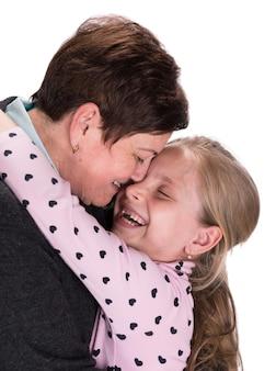 Nonna che bacia nipote su un muro bianco