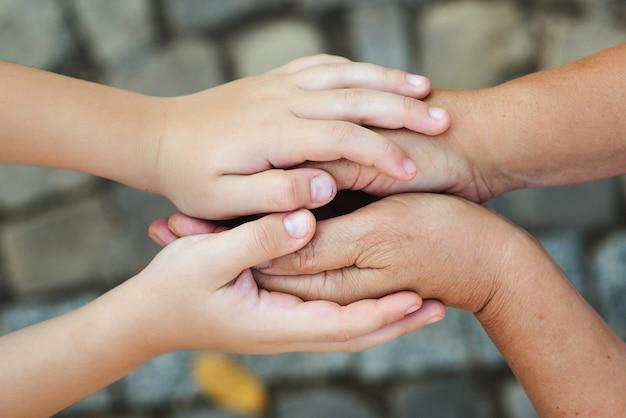 Nonna e bambino che si tengono per mano. chiuda in su dell'anziano e del bambino che si tengono per mano. concetto di famiglia, cura e supporto. nonno con nipote.