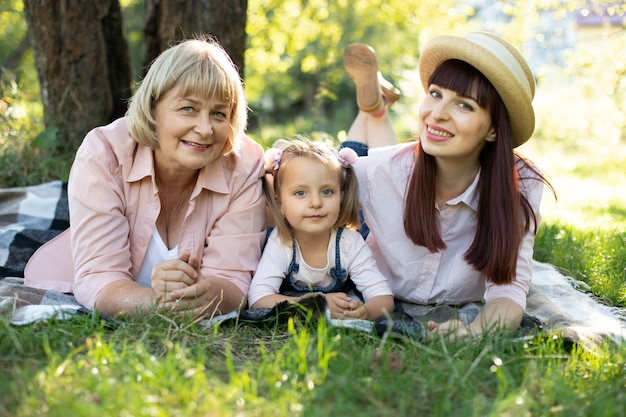 Nonna, madre e nipote che si godono la vacanza soleggiata in giardino insieme all'aperto, sdraiati sull'erba verde su una coperta e sorridenti. stile di vita familiare per il tempo libero, felicità e momenti.