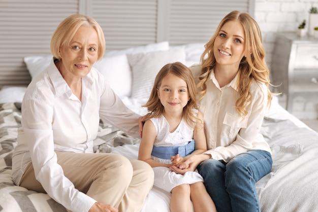 Nonna, madre e la sua piccola figlia sedute sul letto e legate tra loro, mentre entrambe le donne abbracciano un bambino e sorridono.