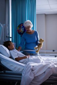 Nonna che mostra orsacchiotto al nipote