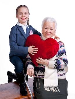 Nonna con la nipote che tiene cuscino cuore su sfondo bianco