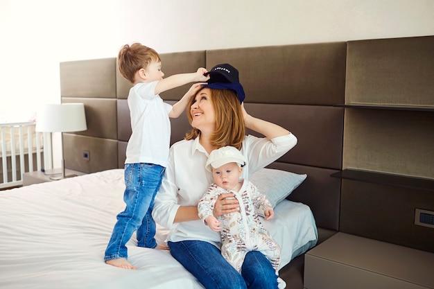Nonna con nipoti seduta sul letto in camera