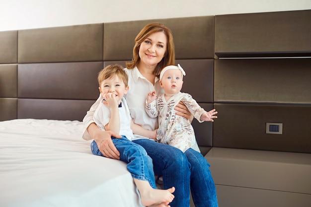Nonna con nipoti seduta sul letto in camera.