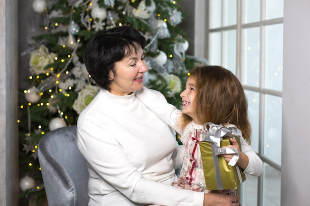 Nonna con una bambina sullo sfondo di addobbi natalizi e una grande finestra
