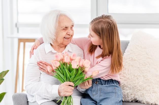 Nonna con i fiori dei tulipani nelle sue mani con la nipote in età prescolare che si abbraccia e si guarda l'un l'altro