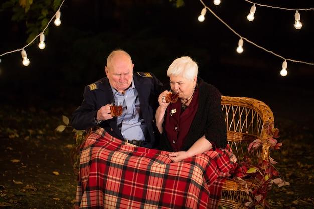 Il nonno e la nonna bevono il tè nel parco.