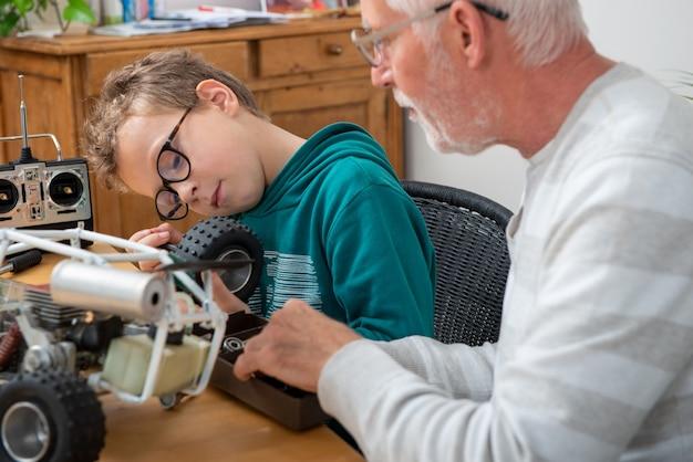 Nonno e figlio ragazzino che riparano un modello di automobile radiocomandata