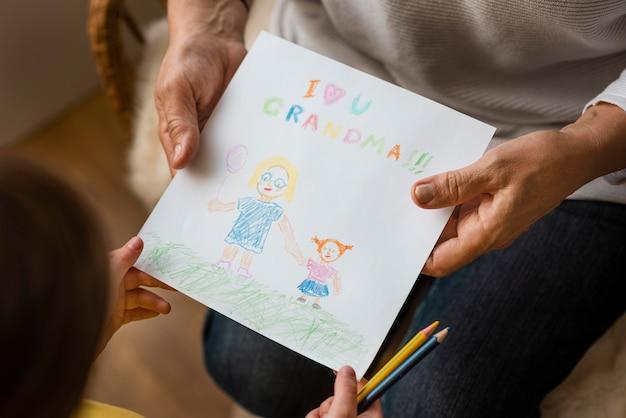 Nonno che tiene il disegno da vicino