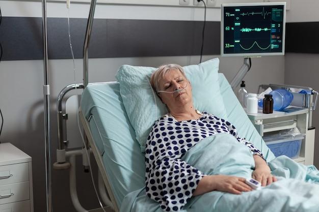 Nonno con problemi respiratori inspira ed espira con l'aiuto della maschera di ossigeno, sdraiato nel letto d'ospedale