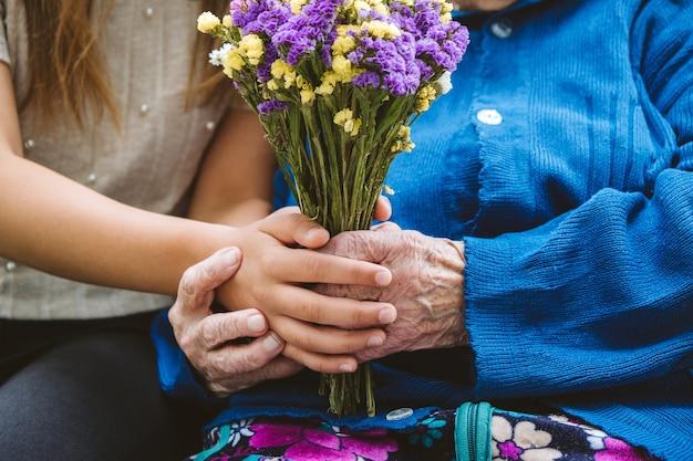 Il giorno dei nonni ha riunito la famiglia la nonna anziana anziana abbraccia la nipote all'aperto