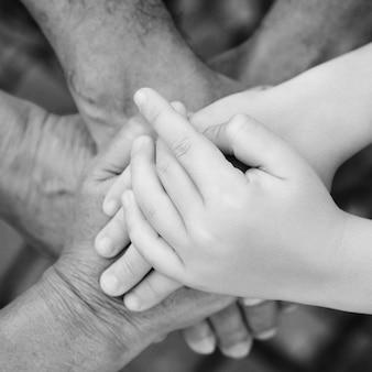 Nonni con nipote che si tengono per mano insieme, vista dall'alto. concetto di famiglia, cura e supporto. il concetto di prendersi cura matura insieme.