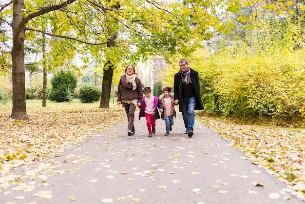 Nonni con i nipoti nel parco di autunno