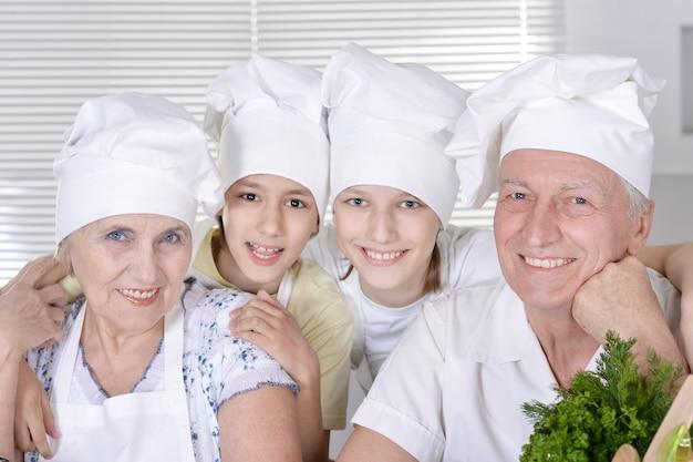 I nonni con due ragazzi stanno preparando la cena per la famiglia