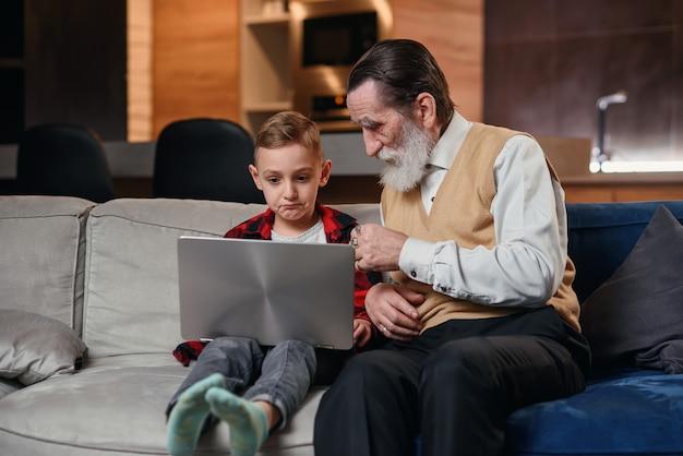 Il nipote sta insegnando a suo nonno a usare il computer portatile.