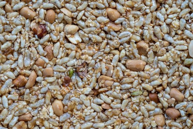 Barretta di muesli. spuntino dolce e salutare. arachidi e riso con miele sullo sfondo, primo piano, vista dall'alto