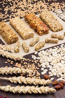 Barretta ai cereali. spighette di grano, chicchi di grano, farina d'avena. cibo vegetariano dieta sana. vista dall'alto. superficie in legno scuro. avvicinamento