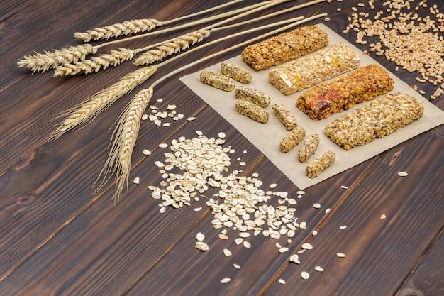 Barretta ai cereali. spighette di grano, chicchi di grano, farina d'avena. cibo vegetariano dieta sana. vista dall'alto. superficie in legno scuro. copia spazio