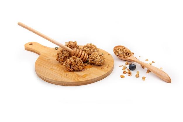 Morsi di muesli con miele su un tagliere di legno con un cucchiaio di legno isolato su sfondo bianco