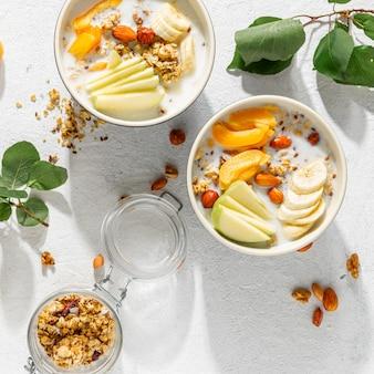 Cereali muesli con frutta, noci, latte e burro di arachidi in una ciotola su uno sfondo bianco. vista dall'alto di cereali per la colazione sana