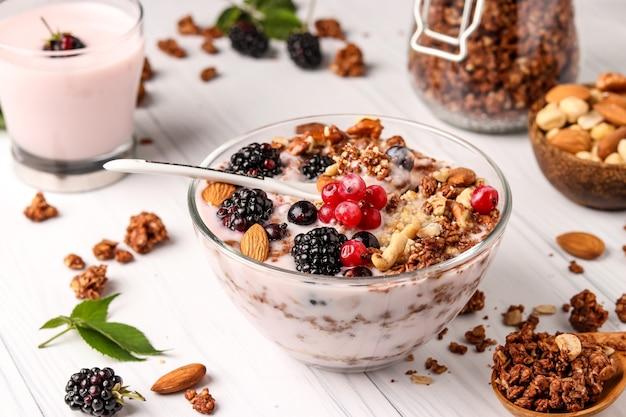 Muesli croccante al miele con yogurt naturale, frutti di bosco freschi, cioccolato e noci in una ciotola su uno sfondo chiaro