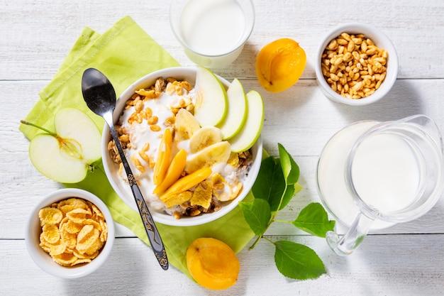 Muesli e yogurt vegetariano con fette di mela, albicocca, banana e una brocca di latte su un fondo di legno bianco.