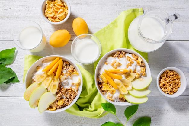 Muesli e yogurt vegetariano con fette di mela, albicocca, banana e una brocca di latte su una superficie di legno bianca. concetto di colazione sana. vista dall'alto