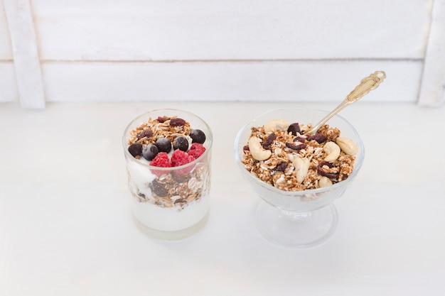 Muesli con frutti di bosco e yogurt su uno sfondo bianco. colazione americana tradizionale