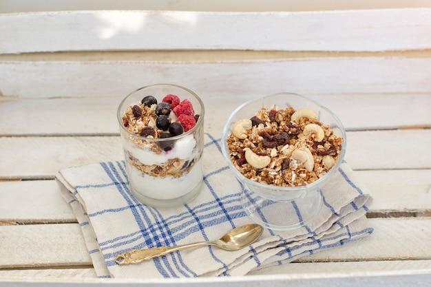Muesli con frutti di bosco e yogurt su un tavolo di legno. colazione americana tradizionale