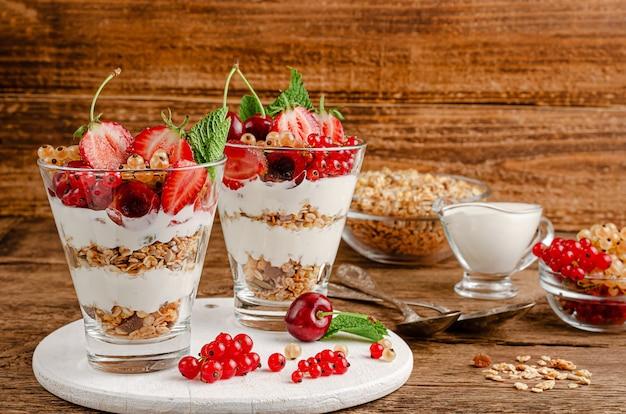Muesli con frutti di bosco freschi e yogurt su sfondo di legno, copia dello spazio