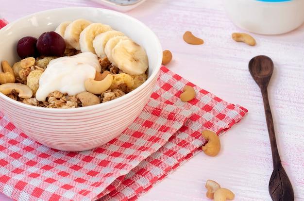 Muesli con frutti di bosco e noci con yogurt in un piatto