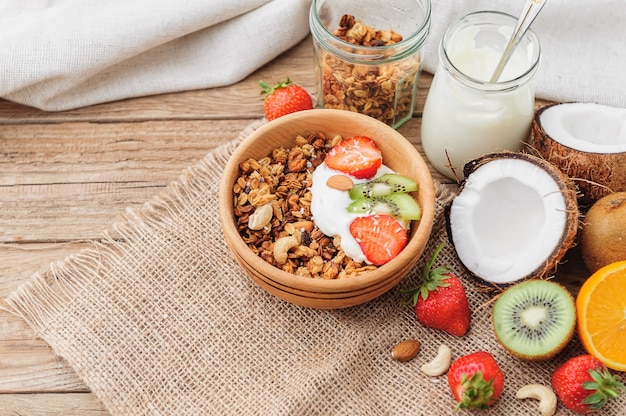 Muesli con yogurt greco e frutta su fondo di legno in stile rustico