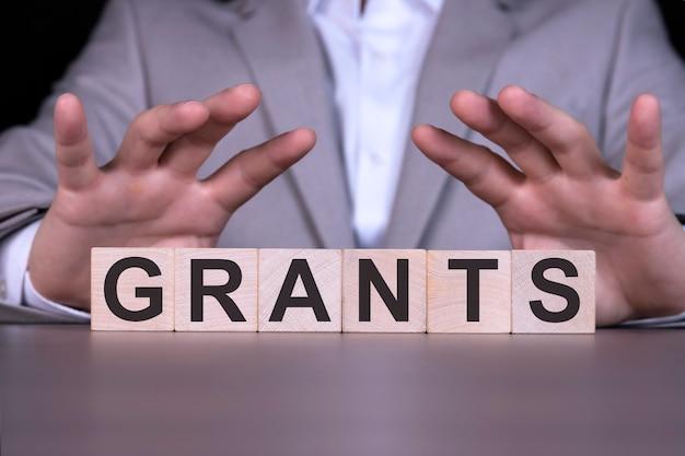 Sovvenzioni, la parola è scritta su cubi di legno, sullo sfondo un uomo d'affari in abito grigio.